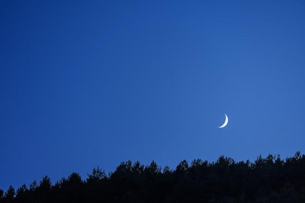 Mince croissant de lune dans le ciel bleu du crépuscule