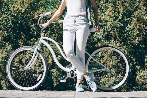 Mince jeune femme dans un t-shirt blanc et un jean se tient près de son vélo élégant en été
