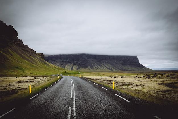 Une mince route dans un champ vert avec des collines et un ciel nuageux gris en islande