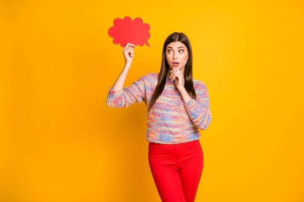 Minded étonné fille tenir le nuage de carte de papier rouge pense que les pensées décident de choisir le dilemme réponse toucher les mains menton hésiter doute porter bon look copyspace pull couleur brillance isolé