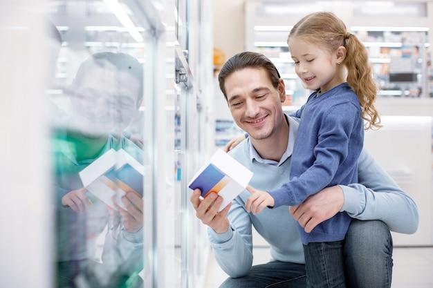 Minéraux nécessaires. homme exubérant positif transportant des médicaments tout en serrant la fille