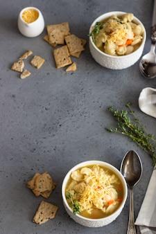 Minestrone avec des pâtes et des haricots blancs garnis de thym et servis avec des craquelins