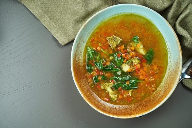 Minestrone - une soupe italienne classique à base de légumes de saison avec l'ajout de riz ou de pâtes dans un bol bleu sur une table en bois. vue de dessus, espace copie