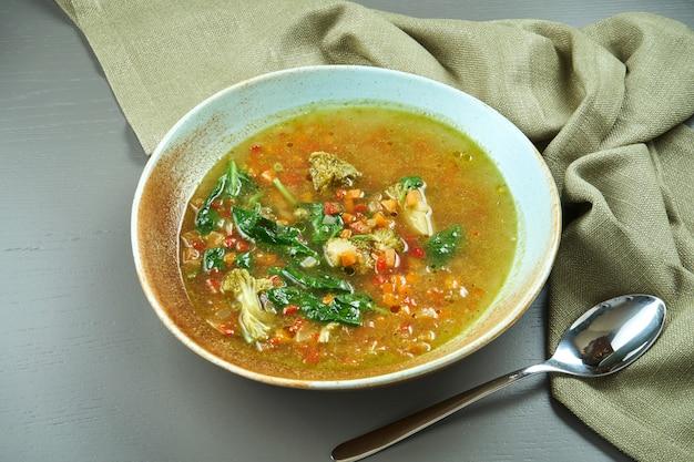 Minestrone - une soupe italienne classique à base de légumes de saison avec l'ajout de riz ou de pâtes dans un bol bleu sur une table en bois