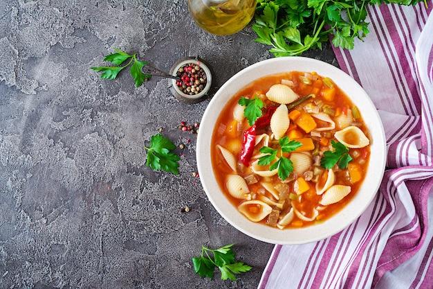 Minestrone, soupe de légumes italiens avec des pâtes sur la table. nourriture végétalienne. vue de dessus