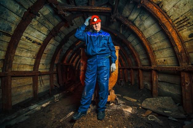 Un mineur dans une mine de charbon se trouve près d'un chariot. espace de copie.
