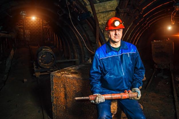 Mineur avec un marteau-piqueur assis sur un chariot dans une mine de charbon