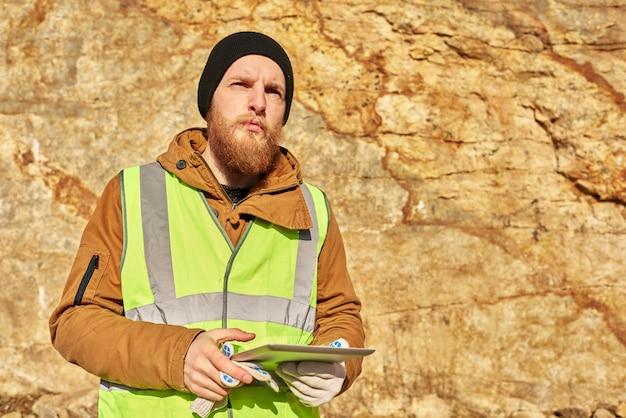Mineur d'or barbu inspectant des terres