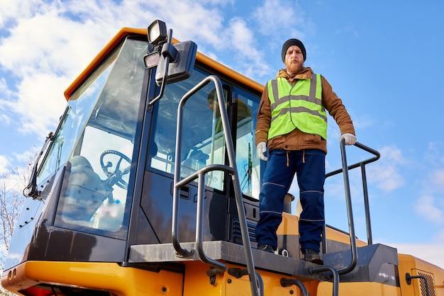 Mineur d'or barbu posant sur un camion
