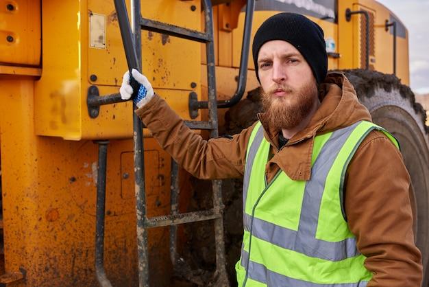 Mineur d'or barbu posant avec camion