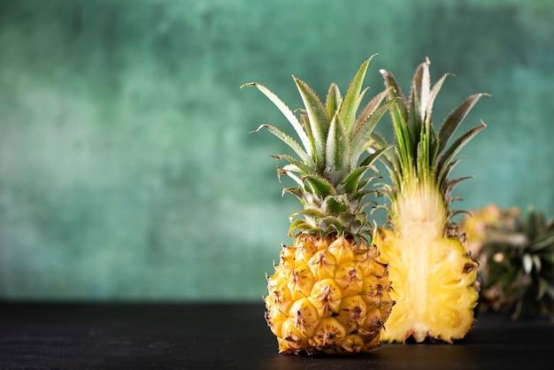 Mini ananas frais coupé sur fond vert, gros plan