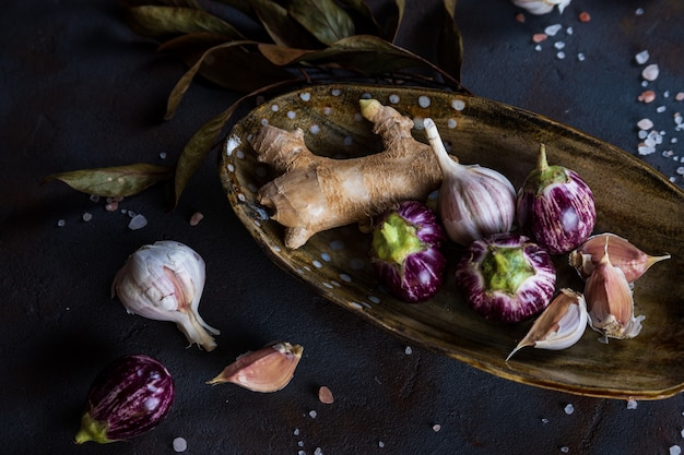 Mini aubergines, gingembre, ail dans une assiette en céramique faite à la main, sel rose cristallin sur béton