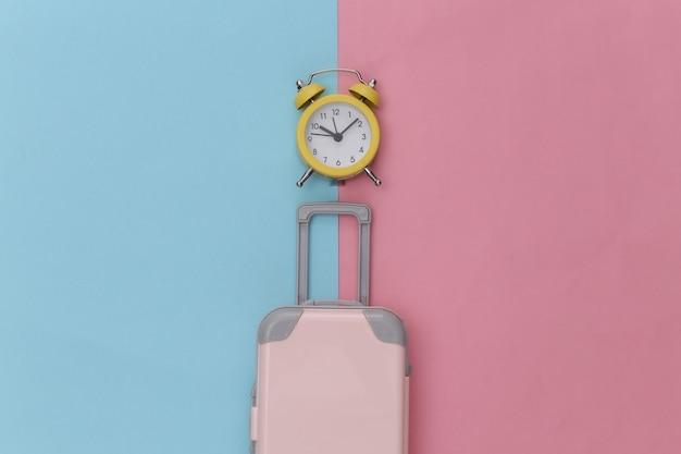 Mini bagage et réveil sur fond pastel bleu rose.