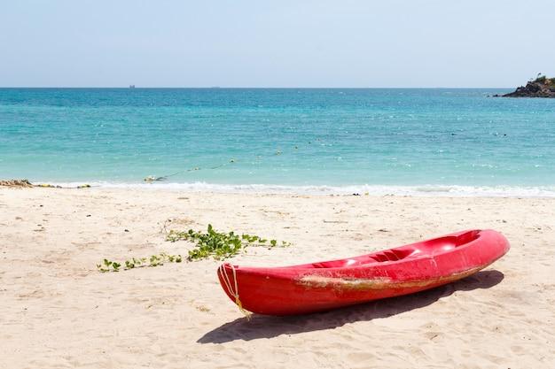 Mini bateau rouge sur la plage
