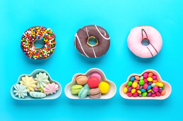 Mini bonbons colorés dans un bol en forme de nuage avec beignets isolés