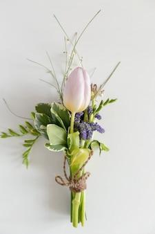 Mini bouquet de fleurs bleues, de tulipes et de freesias
