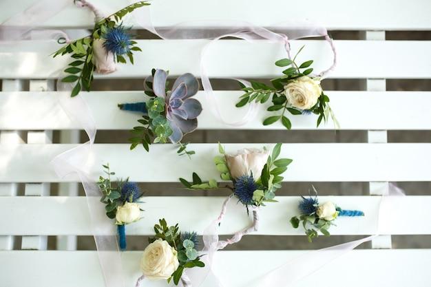 Mini bouquets de fleurs fraîches sur une clôture décorative en bois blanche