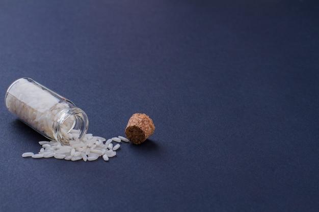Mini bouteille ouverte avec du riz allongé sur une surface bleu foncé. tas de riz blanc.