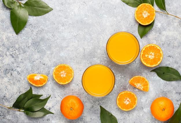 Mini bouteilles en plastique de jus d'orange frais bio avec des oranges et des mandarines crues
