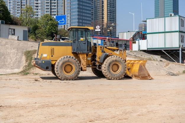 Mini bulldozer de chantier de construction de bâtiment industriel nivelant et remuant le sol pendant la construction d'une autoroute