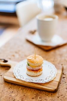 Mini-burger au poulet sur une planche à découper en bois avec une tasse de thé flou et une tasse en arrière-plan.