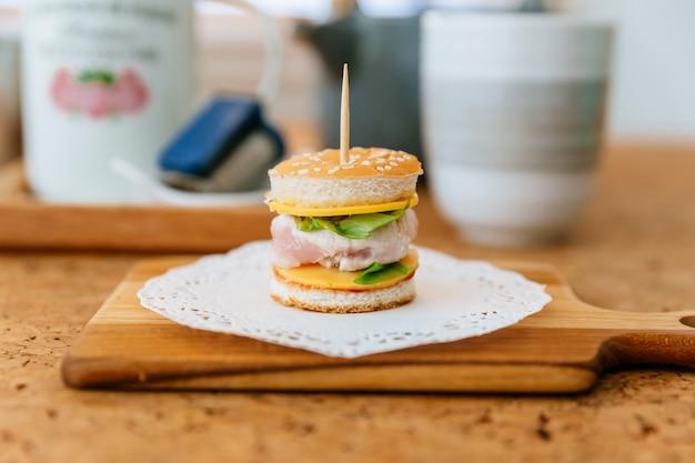 Mini burger de poulet sur une planche à découper en bois avec une tasse de thé flou et une tasse en arrière-plan.