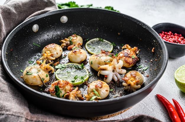 Mini calamars grillés au citron vert et aux épices dans une poêle. vue de dessus