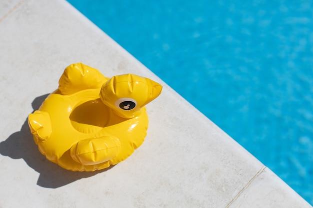 Mini canard jaune gonflable, stand de cocktail près de la piscine par une journée ensoleillée, copiez l'espace. vue de dessus.