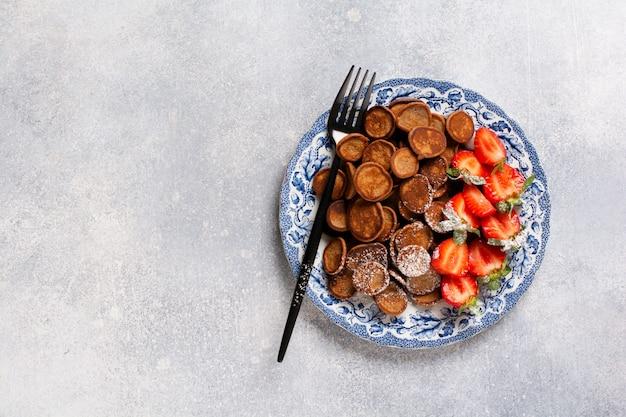 Mini céréales crêpes au chocolat avec des fraises pour le petit déjeuner sur table en béton gris