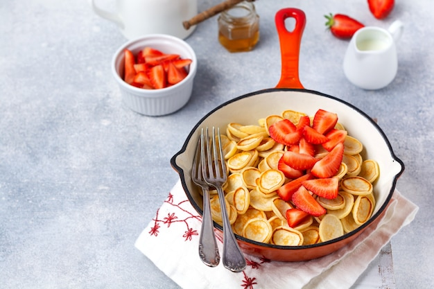 Mini céréales crêpes blanches aux fraises dans une poêle pour le petit déjeuner sur une surface grise. vue de dessus.