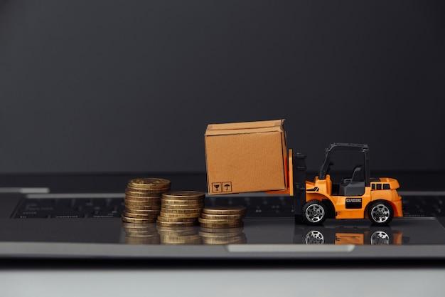 Mini chariot élévateur avec des boîtes en carton et des pièces de monnaie sur le clavier