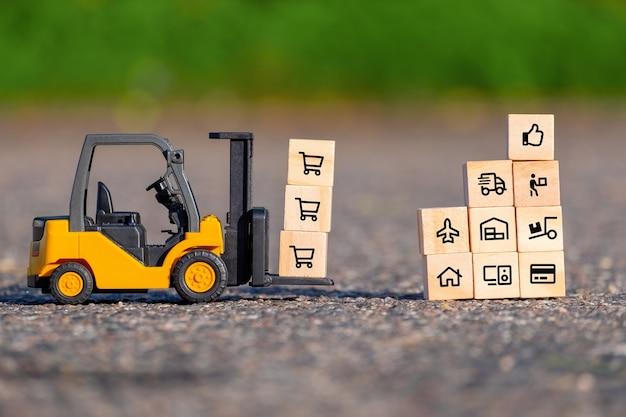 Mini chariot élévateur déplace une palette avec un bloc en bois avec des icônes