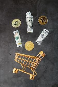 Mini chariot d'or avec des pièces de monnaie bitcoin et des dollars américains dans un vol de lévitation sur une surface sombre