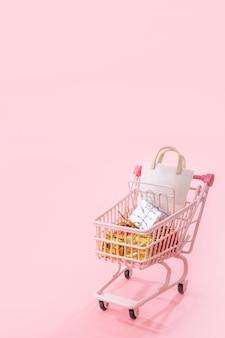 Mini chariot rose de chariot plein de cadeau de sac de papier avec l'espace de copie