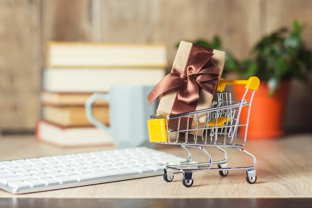Mini chariot de supermarché avec boîte-cadeau sur le bureau avec clavier, réveil et tasse.