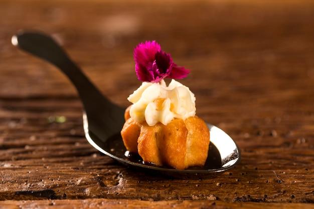 Mini churros salés, accompagnés d'une réduction de café aromatisé au kombu et farcis de fromage à la crème à l'orange confite dans une cuillère. goûtez la fingerfood de la gastronomie