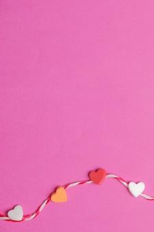 Mini coeurs avec une corde en arrière-plan rose blanc