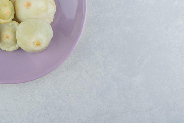 Mini courgettes marinées dans une assiette sur la surface en marbre
