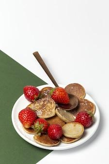 Mini crêpe de céréales maison avec du yaourt, du miel et des fraises sur une table colorée.