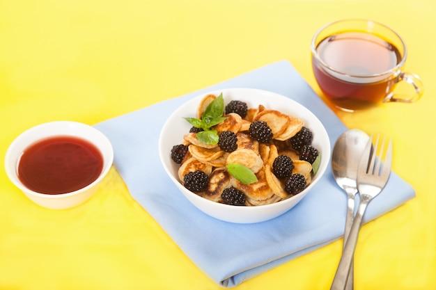 Mini crêpes aux mûres et à la menthe dans une tasse, une tasse de confiture et une tasse de thé. flatlay.