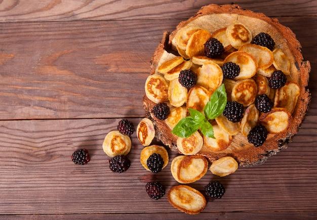 Mini crêpes aux mûres et à la menthe sur un support en bois se tiennent sur une table en bois.