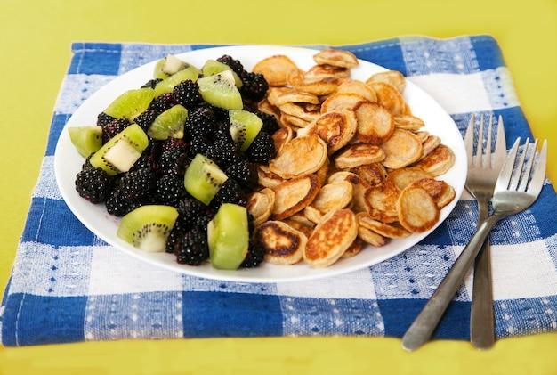 Mini crêpes aux mûres et tranches de kiwi sur une assiette, deux fourchettes sur une serviette en lin bleu. dessert.