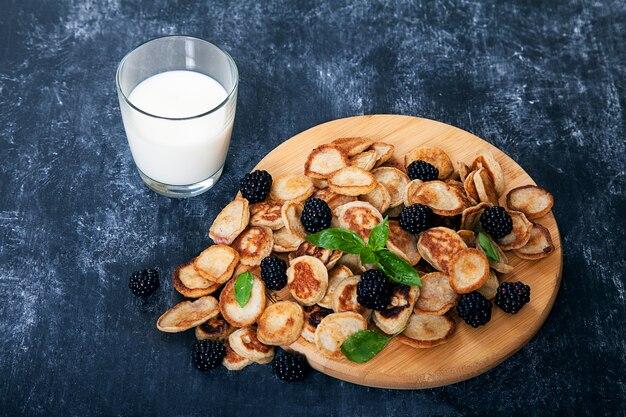 Mini-crêpes et mûres, un verre de lait. dessert.