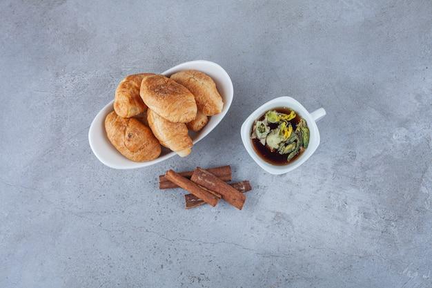 Mini croissants en pâte feuilletée avec une croûte dorée et une tasse de thé.