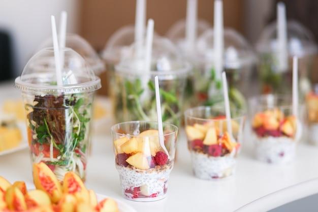 Mini-desserts et salades végétales saines aux micro-légumes dans des canapés en plastique.