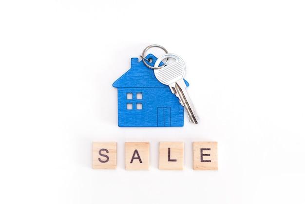 Mini figure bleue de maison avec des clés sur un fond blanc d'isolement. vente d'inscription de lettres en bois