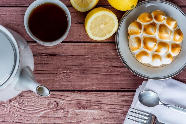 Mini gâteau au citron, citrons et tasse de thé.