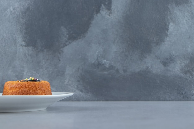 Un mini gâteau avec de la gelée placé sur une assiette blanche. photo de haute qualité