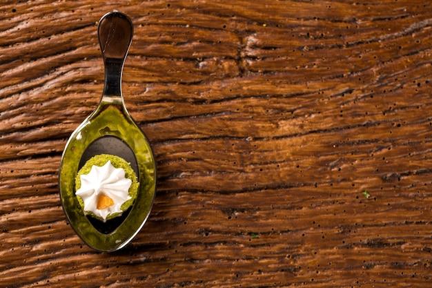 Mini gâteau nu de jus de citron farci de gelée de cupuaçu, praliné de noix et meringue suisse dans une cuillère. goûtez la fingerfood de la gastronomie