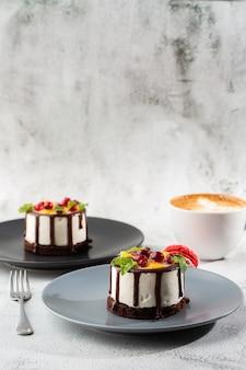 Mini gâteau soufflé rond aux fruits et glaçage au chocolat sur topc sur fond de marbre. fond d'écran pour pâtisserie ou menu de café. verticale.